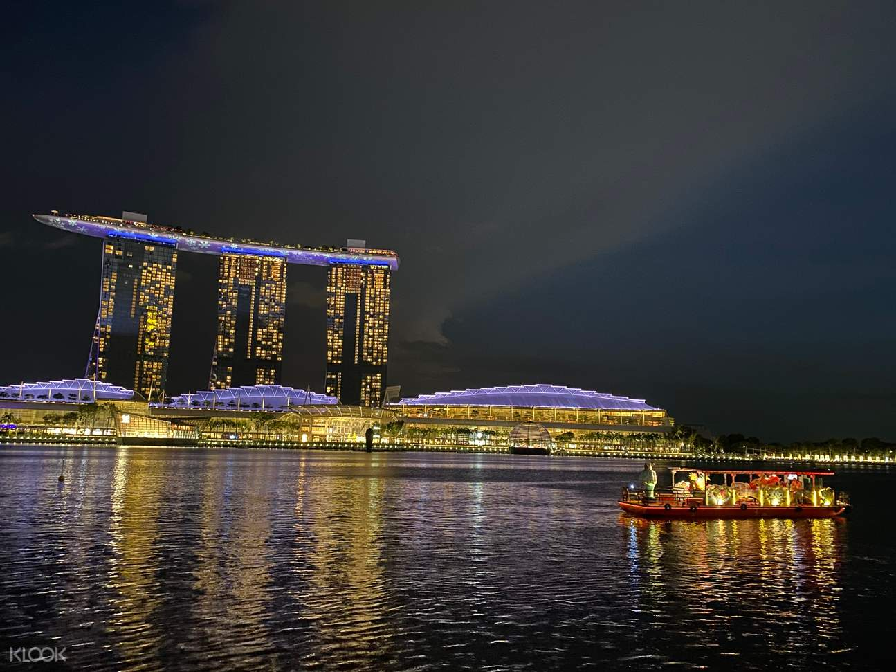 marina bay sands at night with a boat nearby